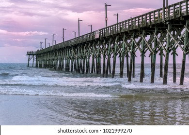 Long dock and mild waves at the beach during sunset