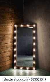 Long dressing mirror with light bulbs stands on the floor against a wooden and concrete wall