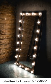 Long dressing mirror with light bulbs stands on the floor against a wooden and concrete wall side view