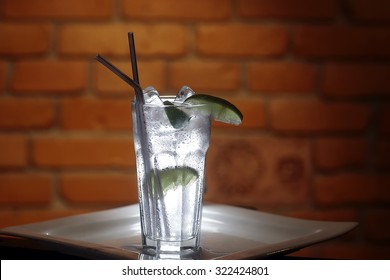 Long drink gin tonic cocktail with ice cubes and slices of lime in glass with two straws standing on white square plate on brown brick wall background, horizontal photo