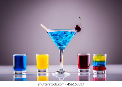 Long drink; glass of blue curacao with colored alcoholic shots