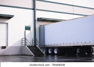 Long dry van semi trailer with dual axles loading and unloading commercial cargo in concrete walls warehouse dock with gates and steps