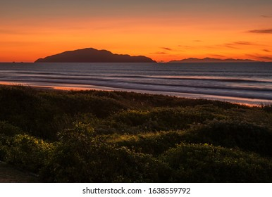 Long duration exposure of the remains of a sunset with Kapiti Island of New Zealand on the horizon and blurred waves with long exposure