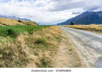 Long dusty country road through mountains and fields along Lake Wakatipu in Otago, New Zealand.