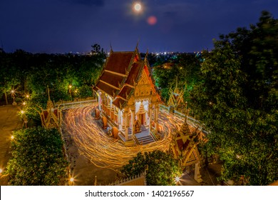 Long eaposure of Buddhism light waving rite walk with candles ighted in hand around temple with full moon night at Wat Nongprong in Buriram, Thailand.