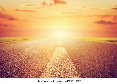 Long empty asphalt road towards sunset sun. Wide perspective, conceptual way