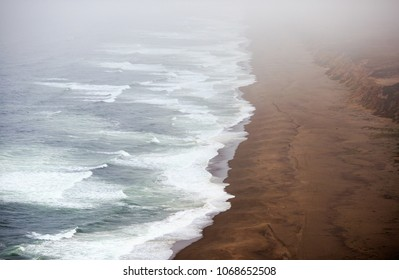 Long empty beach disappears into dense low fog on the northern California coast