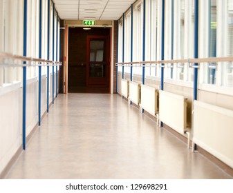 long empty corridor with an emergency exit sign