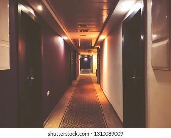 Long empty dark corridor with many doors in vintage style, toned.