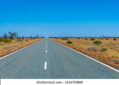 Long empty road in Australia leading through savanna landscape touching the horizon