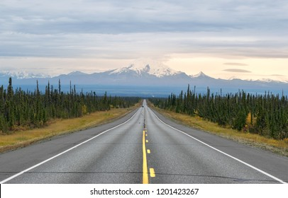 Long empty road with mountain range in the background