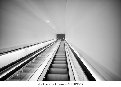 Long escalator set in bright light with a nice line towards a vanishing point in the middle.
