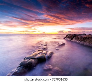 Long expose sunset seascape with green moss at Sabah, Malaysia. Image contain soft focus and blue due to long expose and water movement.