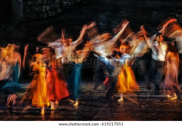 Долгое выставлено и красочное фото танцоров, исполняющих свое искусство в мюзикле.
