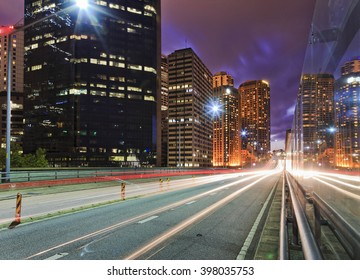 Long exposed trails of headlights and back lights of passing vehicles at sunset along high speed motorway in Sydney CBD at sunset between high-rise towers.
