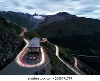 long exposure aerial shot on winding swiss alps mountain pass road, light trails of road traffic, small glacier and steep ridge in the distance