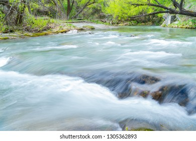 Long exposure Arrow River flowing fast through gorge lined with lush green deciduous trees