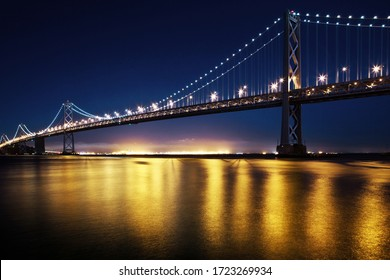 a Long Exposure of the Bay Bridge in San Francisco at Night with Lights Reflecting over the Water