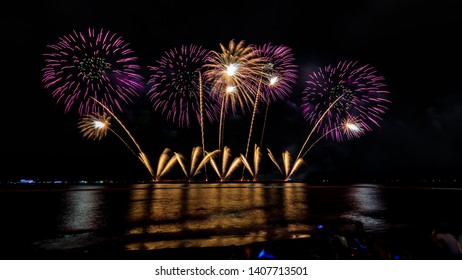long exposure beautiful celebrations firework over colorful at night on the sea and  reflections water front on dark background pattaya city Thailand