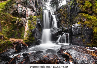 Long exposure of a beautiful remote waterfall in northern Minnesota, surrounded by rocks and green moss.