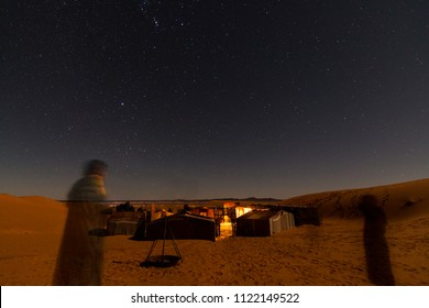 Long exposure of the berber men standing in front of berber camp tents in the moroccan sahara desert in africa
