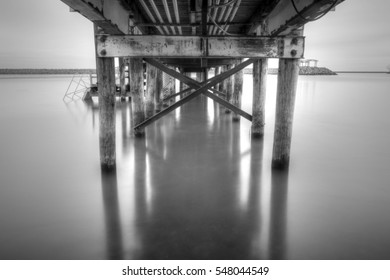 Long exposure black and white daytime picture of wooden dock with metal bracing extending out into Lake Erie with stone seawall in background in Buffalo, New York