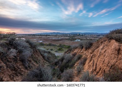 Long exposure bluff top view of Ballona Wetlands at sunset with colorful sky and Santa Monica Mountains in the distance, Playa Del Rey, California