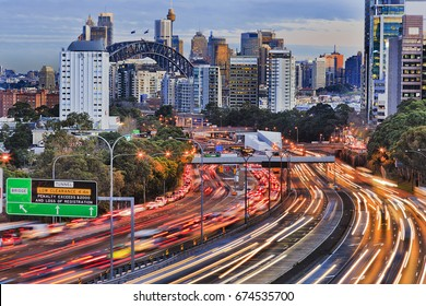 Long exposure blurred vehicle motion on multi-lane Warringah freeway going through North Sydney in Sydney, Australia. Headlights during rush hour commute towards Sydney harbour bridge and CBD towers.