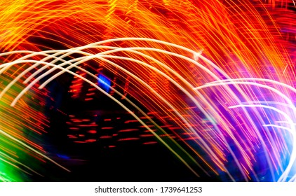 Long exposure of bright colored fairground light trails