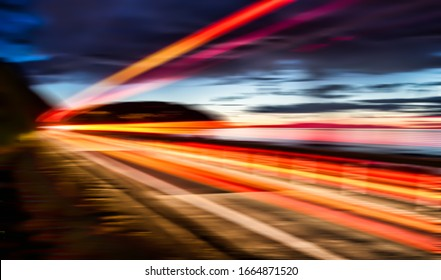 Long exposure capturing  red and orange light trails from a speeding truck at the coast