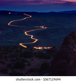 A long exposure of cars leaving Arches National Park at sunset