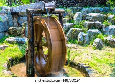 Long exposure closeup of waterwheel in motion as water empties from trough above into pool below. Motion blur created by long exposure for effect.