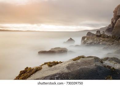 long exposure deep blue sea ocean rock and green plant at qaqortoq greenland