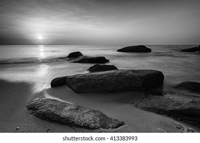 Long exposure during sunrise with dual tone color as background and boulders as the subject in black and white.