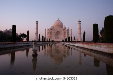 A long exposure at dusk blue hour gives a ghostly appearance to an empty front facade and promenade water fountain pool of the Taj Mahal at sunset closing time in Agra, India. Horizontal copy space