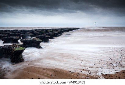 Long exposure Felixstowe Breakwater in storm conditions at low tide with waves breaking against and through the sea defence onto the beach