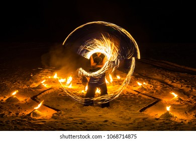 Long exposure fire twirler performer dancing with circular fire rod light effects on the beach at summer night.
