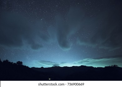 Long exposure and High ISO shot of star and cloud over the mountain at night. blue tone effect.