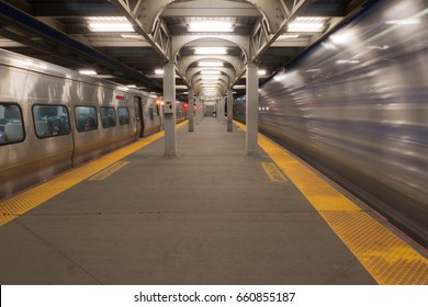 Long Exposure of high speed express train passing station platform waiting departing train at railroad terminal hub. Motion blur right side, stationary on left