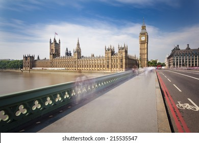 Long exposure of the Houses of Parliament in London with blue sky seen from the Westminster Bridge with some blurred people.