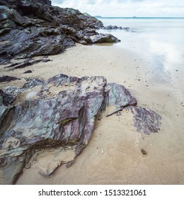 A long exposure image of the beach at Hayle Bay, Cornwall, England UK on a sunny day with rocks and sand.