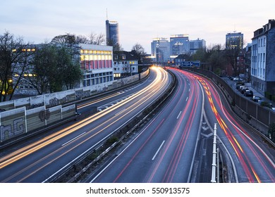 Long exposure image of cars racing past the skyline of Essen, Germany at dusk