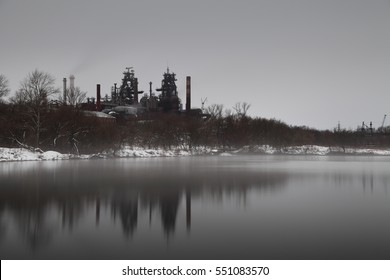 Long exposure image of industrial plant near pond with steam on water