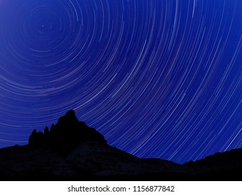 Long exposure image showing Night sky star trails over mountains