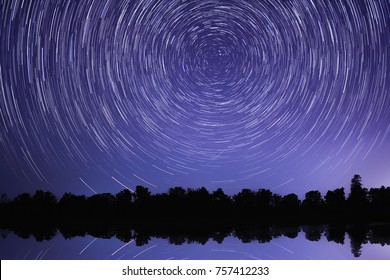 Long exposure image showing star trails over lake