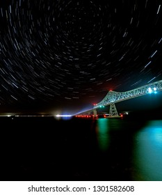 A long exposure image of stars trailing across the sky as the earth turns through the night and the Astoria Megler bridge over the Columbia river.