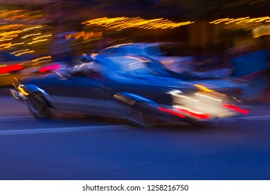 Long exposure impressionistic image of a car speeding by neon lights on a city street at night