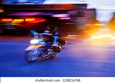 Long exposure impressionistic image of two motorcyclists outdistancing city traffic alongside neon lights at night