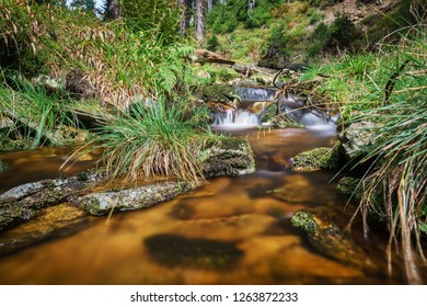 Long exposure of iron colored river Hučivá Desná in Jeseniky mountains in the Czech republic