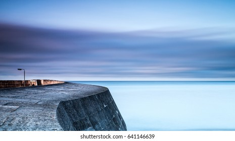 Long exposure of a jetty curling away into a calm sea with sunrise striking the east wall.